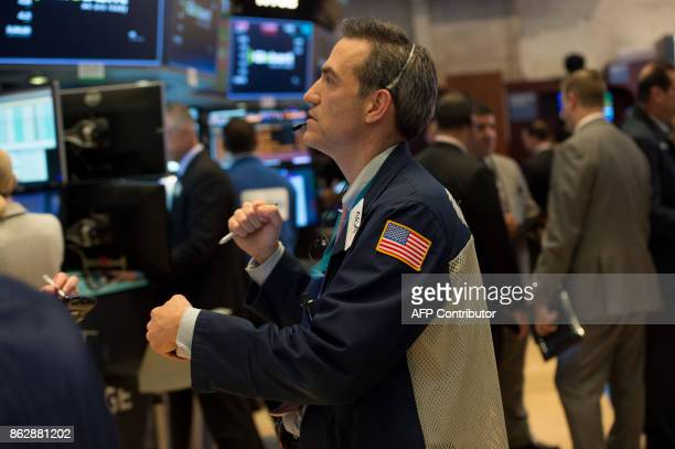 A trader reacts to the Dow closing above 230000 for the first time on the floor at the closing bell of the Dow Industrial Average at the New York...
