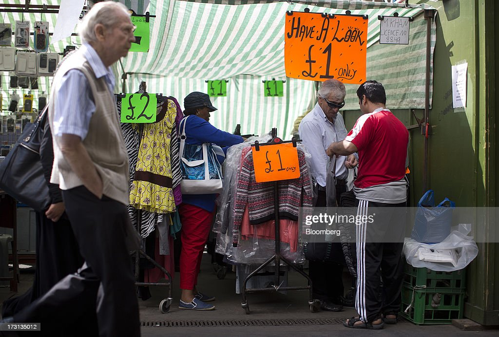 A trader, right, completes a sale with a customer at an outdoor market in London, U.K., on Monday, July 8, 2013. Britain's economy could be in line for a period of 'strong catch-up growth' once it gets through the current weakness, according to Capital Economics Ltd. Photographer: Simon Dawson/Bloomberg via Getty Images
