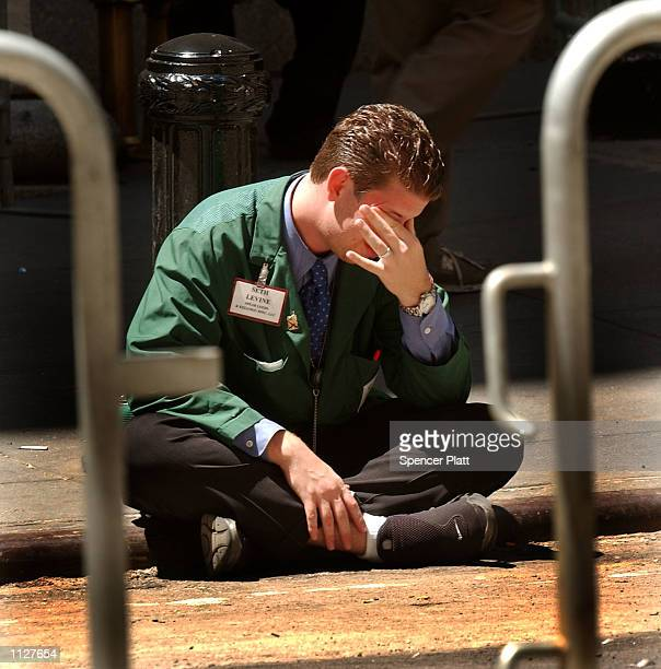 A trader rubs his eyes outside the New York Stock Exchange July 16 2002 in New York City The Dow closed down in seven straight losing sessions...