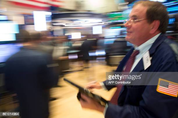 A trader runs across the floor at the closing bell of the Dow Industrial Average at the New York Stock Exchange on October 13 2017 in New York / AFP...