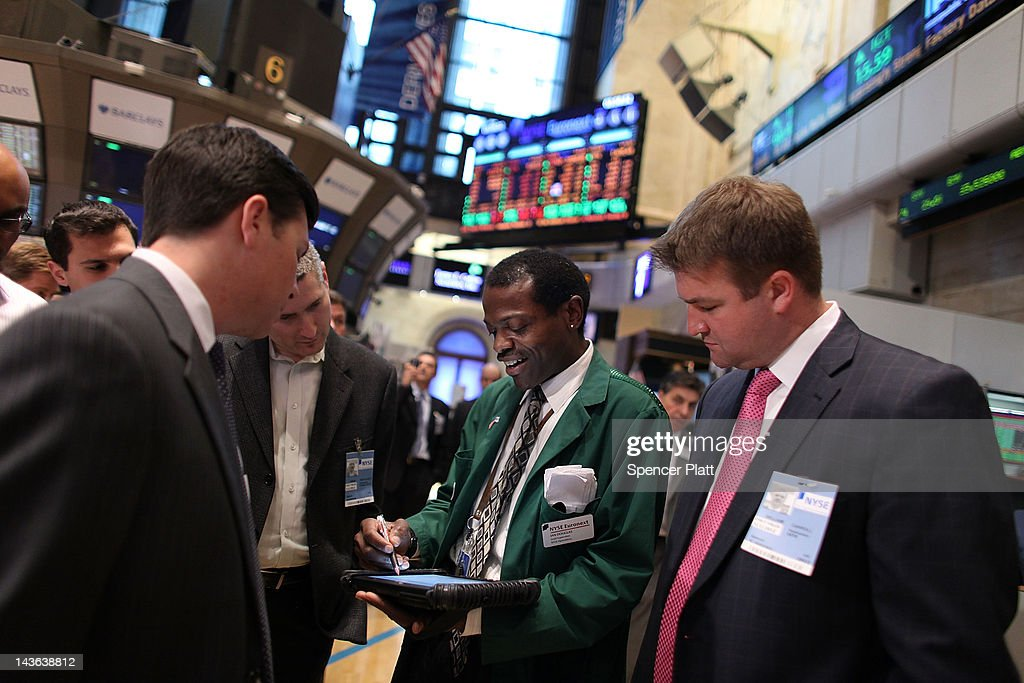 A trader (center) shows guests how the close of the markets works on the floor of the New York Stock Exchange on May 1, 2012 in New York City. Following positive news of a rise in U.S. manufacturing activity, The Dow Jones industrial average rose almost 66 points, or 0.5%, to close at 13,279.40, the highest since December 2007.