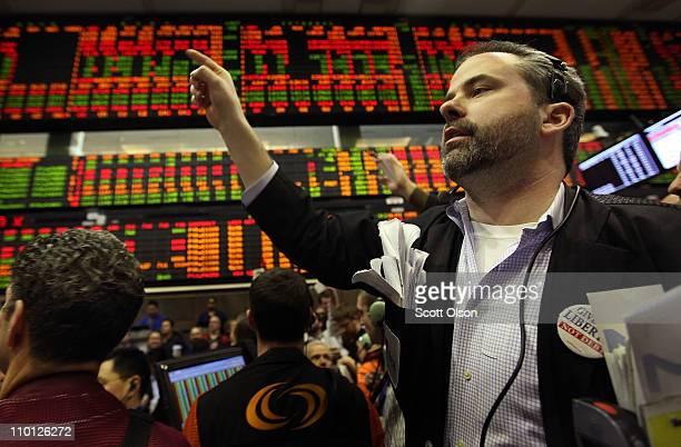 A trader signals an offer in the corn options pit at the CME Group March 15 2011 in Chicago Illinois US stock and commodity prices tumbled today...