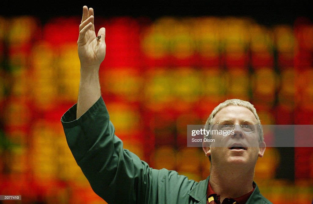A trader signals an offer in the Dow Jones Industrial Average stock index futures pit at the Chicago Board of Trade June 12, 2003 in Chicago, Illinois. The Dow cash index closed at 9,196.44, the highest close in over 11 months.