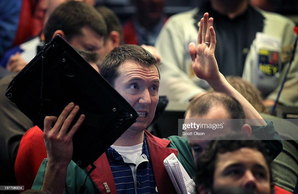 A trader signals an offer in the Standard & Poor's 500 stock index options pit at the Chicago Board Options Exchange (CBOE) following the Federal Open Market Committee meeting on January 25, 2012 in Chicago, Illinois. Following the meeting the Fed, which left interest rates unchanged, said it does not plan any rate changes until late 2014.