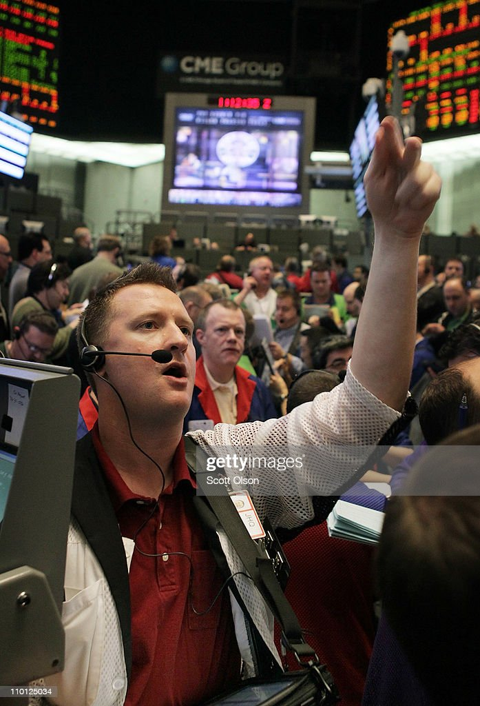 A trader signals an offer in the Ten-Year Treasury Note options pit at the CME Group following the announcement by the Federal Open Market Committee (FOMC) that they would maintain the key policy rate near zero on March 15, 2011 in Chicago, Illinois. U.S. stock and commodity prices tumbled today following a sharp drop in Japan's stock market, as investors worldwide worry about the economic impact of that country's recent earthquake, tsunami and unfolding nuclear crisis.