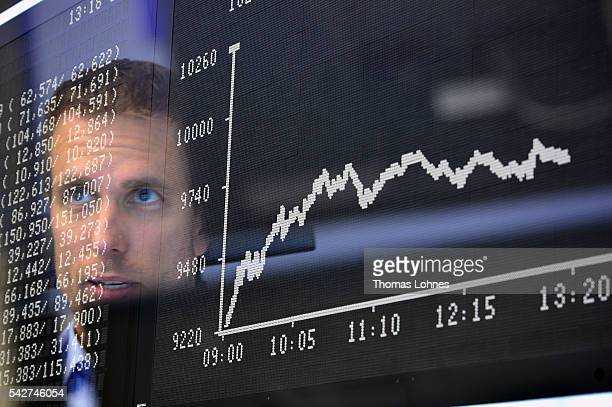 Trader sit at his desk under the day's performance board that shows a dive in the value of the DAX index of companies at the Frankfurt Stock exchange...