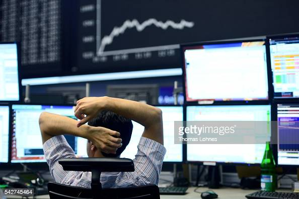 A trader sits at his desk under the day's performance board that shows a dive in the value of the DAX index of companies at the Frankfurt Stock...