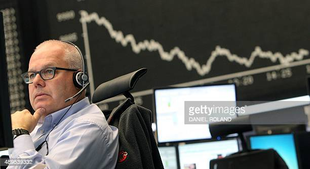 A trader sits in front of a board displaying the chart of Germany's share index DAX at the stock exchange in Frankfurt am Main western Germany on...