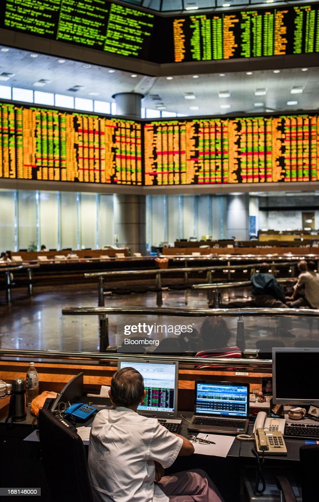 A trader sits in front of computer screens as he works in the trading gallery at the RHB Investment Bank Bhd. headquarters in Kuala Lumpur, Malaysia, on Monday, May 6, 2013. The biggest surge in Malaysian stocks since 2008 has turned into a money-losing day for investors who piled in at the height of the rally sparked by Prime Minister Najib Razak's election victory. Photographer: Sanjit Das/Bloomberg via Getty Images