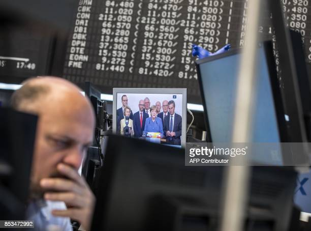 A trader sits next to a screen displaying a report on German Chancellor Angela Merkel and general elections in Germany as he works at the stock...