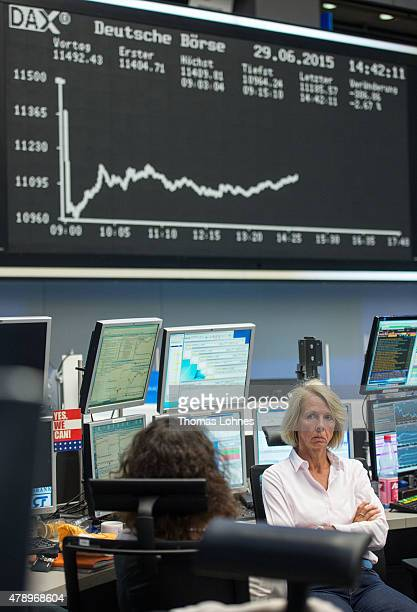 A trader sits under the day's performance graph showing a sharp drop of the German DAX stock market index early today and a partial recovery later on...
