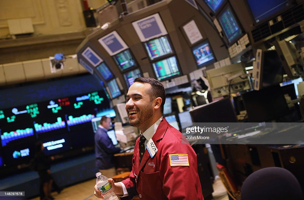 A trader smiles on the floor of the New York Stock Exchange on July 13, 2012 in New York City. The Dow Jones Industrial Average rallied July 13, closing up almost 204 points to finish at 12,777. The rally ended a 6-day slump, the longest since mid-May.