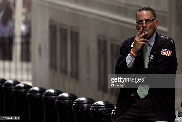 A trader smokes a cigarette outside the New York Stock Exchange in New York US on Wednesday July 8 2015 The New York Stock Exchange shut down its...