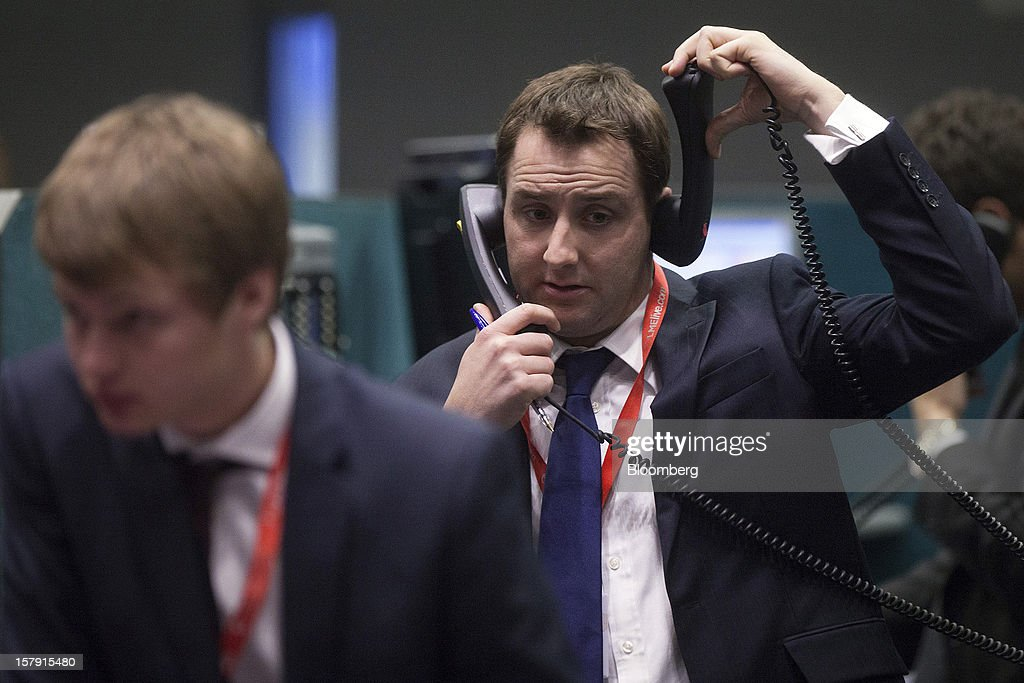 A trader speaks on telephones as he works on the floor of the London Metal Exchange (LME) in London, U.K., on Friday, Dec. 7, 2012. The London Metal Exchange's $2.2 billion takeover by the Hong Kong Exchanges & Clearing Ltd. was completed yesterday. Photographer: Simon Dawson/Bloomberg via Getty Images