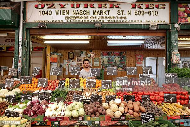 A trader stands in front of fruits and vegetables for sale on his stall at Naschmarkt in Vienna Austria on Friday July 3 2015 Austria broke new...