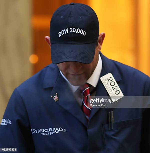 A trader stands outside of the New York Stock Exchange after the Dow Jones industrial average crossed the 20000 mark for the first time on January 25...
