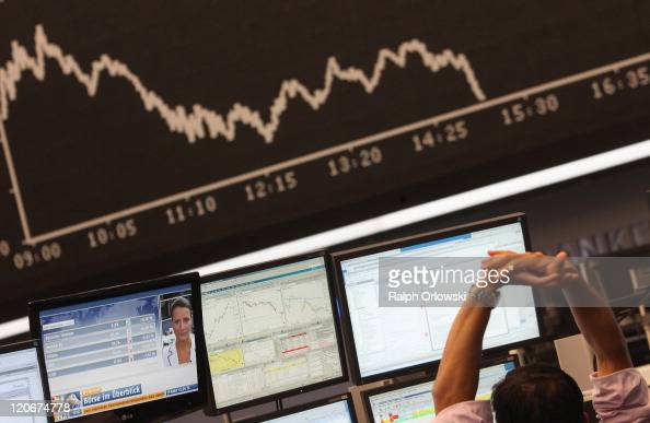 A trader stretches himself in front of a graph showing the day's performance of the DAX index at the Frankfurt Stock Exchange on the first day...