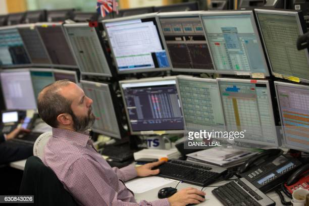 A trader studies information on trading screens at ETX Capital in central London on January 3 2017 London's FTSE 100 reached a historic peak at...