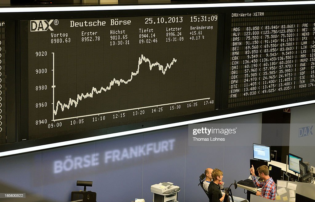 Trader talk under the the day's performance board of the DAX stock market index not long after the DAX broke the 9,000 level at the Frankfurt Stock Exchange on October 25, 2013 in Frankfurt, Germany. Today's level sets a new record for the DAX, which is the main German stock market index.