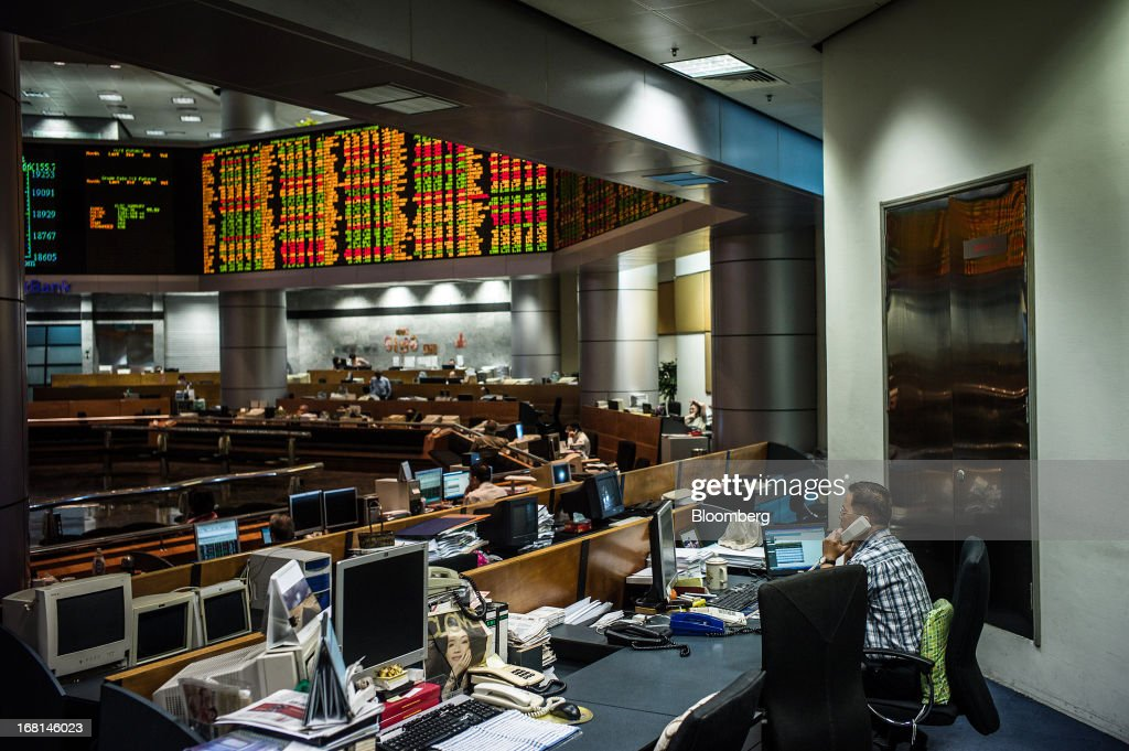 A trader talks on the phone as he works in the trading gallery at the RHB Investment Bank Bhd. headquarters in Kuala Lumpur, Malaysia, on Monday, May 6, 2013. The biggest surge in Malaysian stocks since 2008 has turned into a money-losing day for investors who piled in at the height of the rally sparked by Prime Minister Najib Razak's election victory. Photographer: Sanjit Das/Bloomberg via Getty Images