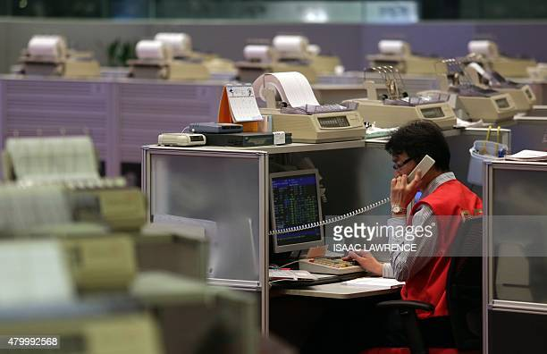 A trader talks on the phone at the Hong Kong Stock Exchange on July 9 2015 Hong Kong shares ended the morning session 343 percent higher July 9...