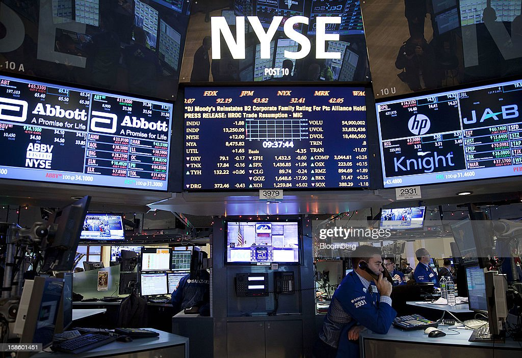 A trader talks on the phone while working on the floor of the New York Stock Exchange (NYSE) in New York, U.S., on Thursday, Dec. 20, 2012. InterContinentalExchange Inc. (ICE), the 12-year-old energy and commodity futures bourse, agreed to acquire NYSE Euronext for cash and stock worth $8.2 billion, moving to take control of the world's biggest equities market. Photographer: Jin Lee/Bloomberg via Getty Images