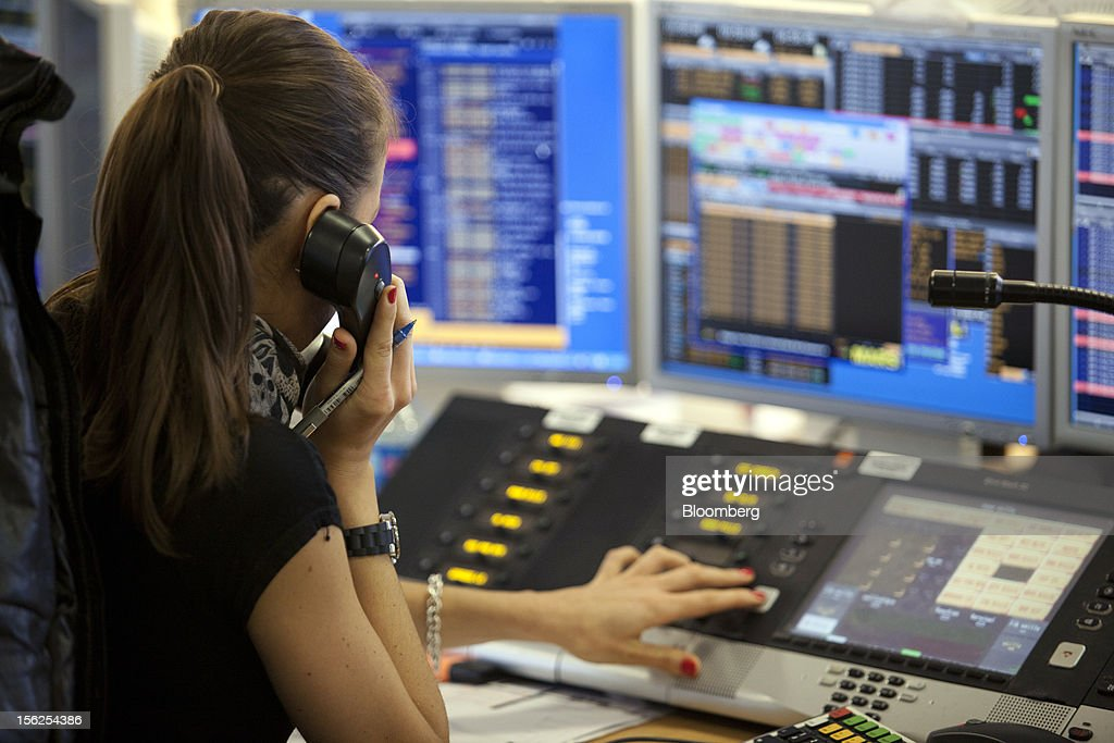 A trader uses a telephone as she works at the Aurel BGC brokerage in Paris, France, on Monday, Nov. 12, 2012. European stocks fluctuated between gains and losses as finance ministers prepared to discuss Greek aid after the country's lawmakers approved the 2013 budget. Photographer: Balint Porneczi/Bloomberg via Getty Images