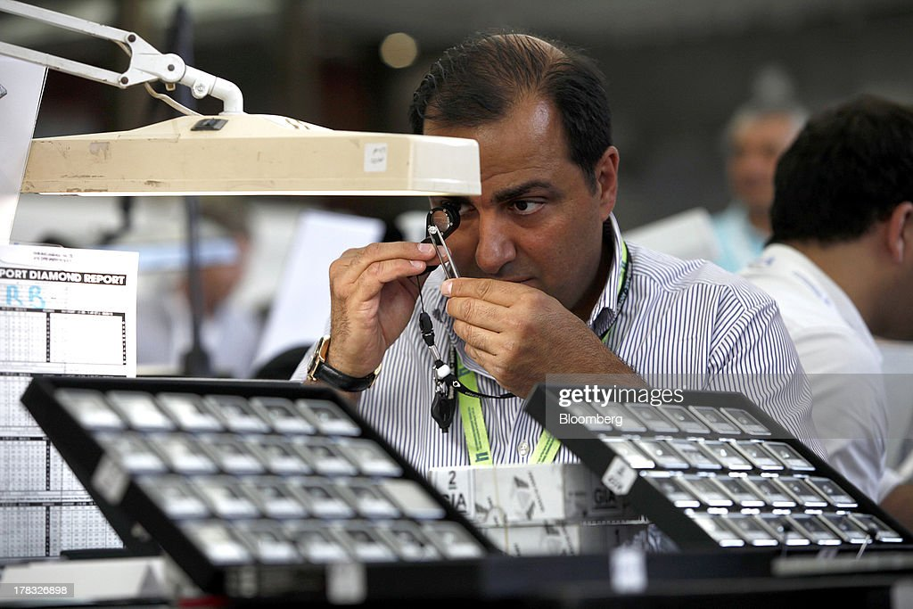 A trader uses an eyeglass to closely inspect a diamond gemstone at a trade fair during International Diamond Week at the Israel Diamond Centre in Ramat Gan, Israel, on Wednesday, Aug. 28, 2013. Diamond prices rose to $7,992 this week from $7,962 a week earlier, according to the Rapaport Diamond Trade Index. Photographer: Ariel Jerozolimski/Bloomberg via Getty Images