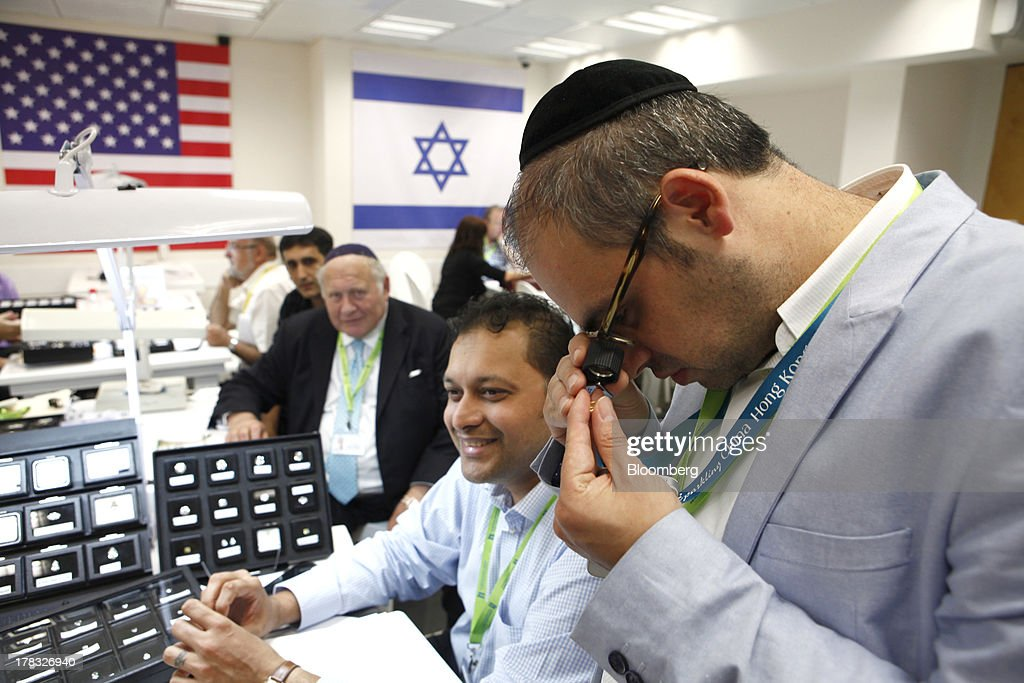 A trader uses an eyeglass to inspect a diamond gemstone at a trade fair during International Diamond Week at the Israel Diamond Centre in Ramat Gan, Israel, on Wednesday, Aug. 28, 2013. Diamond prices rose to $7,992 this week from $7,962 a week earlier, according to the Rapaport Diamond Trade Index. Photographer: Ariel Jerozolimski/Bloomberg via Getty Images