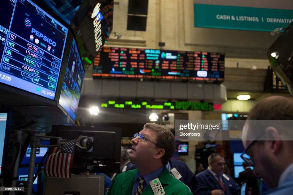 A trader views a monitor while working on the floor of the New York Stock Exchange (NYSE) in New York, U.S., on Wednesday, Jan. 2, 2013. U.S. stocks rose, after the largest year-end rally for the Standard & Poor's 500 Index since 1974, as lawmakers passed a bill averting spending cuts and tax increases threatening a recovery in the world's biggest economy. Photographer: Scott Eells/Bloomberg via Getty Images