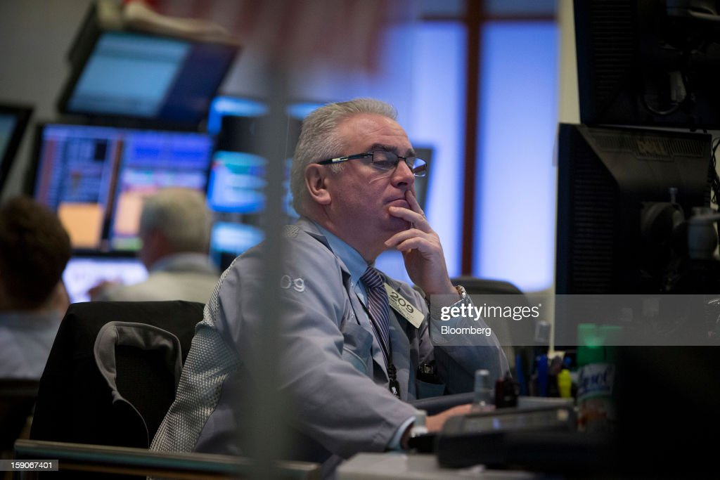 A trader views a monitor while working on the floor of the New York Stock Exchange (NYSE) in New York, U.S., on Monday, Jan. 7, 2013. U.S. stocks fell, after the Standard & Poor's 500 Index climbed to a five-year high, as investors awaited the start of the corporate earnings season tomorrow. Photographer: Scott Eells/Bloomberg via Getty Images