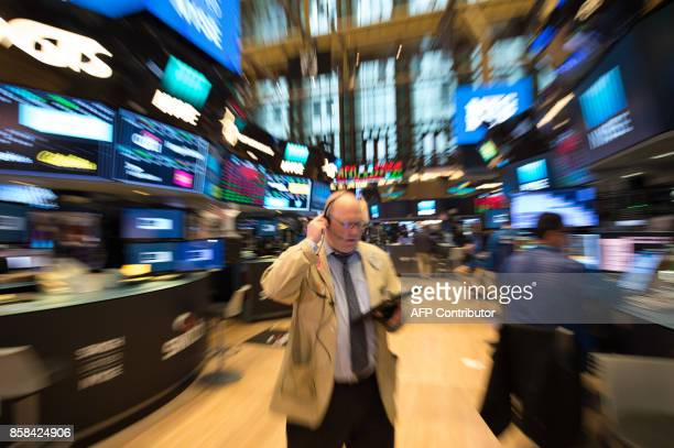 A trader walks across the floor at the closing bell of the Dow Industrial Average at the New York Stock Exchange on October 6 2017 in New York Wall...