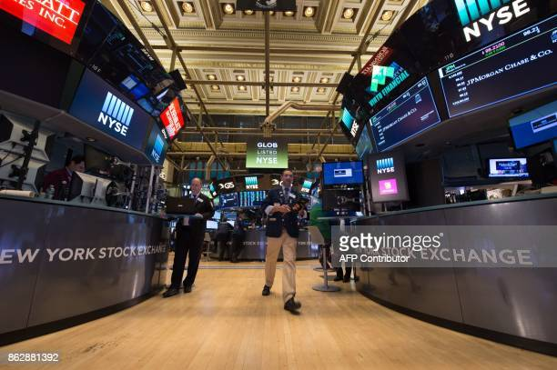 A trader walks across the floor at the closing bell of the Dow Industrial Average at the New York Stock Exchange on October 18 2017 in New York The...