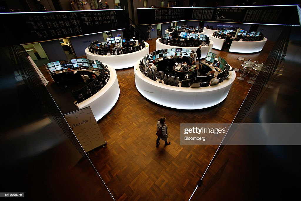 A trader walks across the trading floor below a display of the DAX Index curve at the Frankfurt Stock Exchange in Frankfurt, Germany, on Monday, Sept. 30, 2013. Global stocks fell, trimming their biggest quarterly gain since the start of 2012, while the Japanese yen strenghtened before a potential U.S. government shutdown. Photographer: Ralph Orlowski/Bloomberg via Getty Images