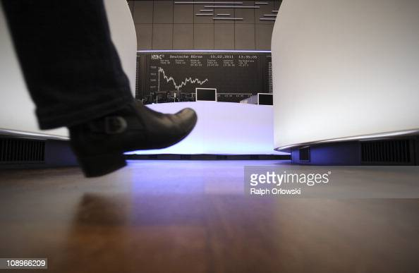 A trader walks along the DAX Index board during a trading session on the main floor of the Frankfurt Stock Exchange on February 10 2011 in Frankfurt...