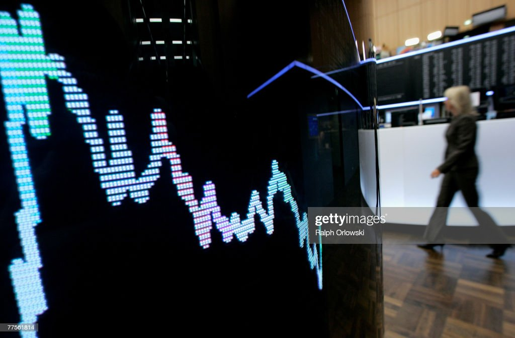 A trader walks behind a display showing the German DAX Index on the trading floor of Frankfurt stock exchange on October 30 2007 in Frankfurt Germany...