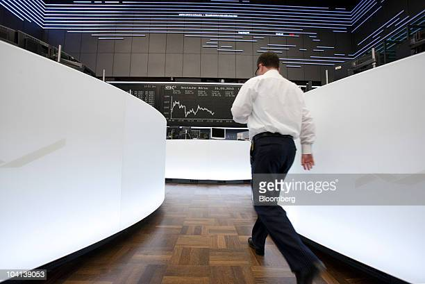 A trader walks in front of the DAX index curve at the Frankfurt Stock Exchange in Frankfurt Germany on Thursday Sept 16 2010 European stocks dropped...