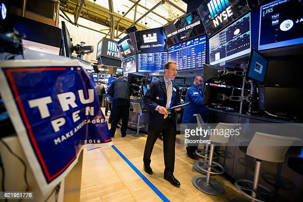 A trader walks past a campaign sign for US Presidentelect Donald Trump and US Vice Presidentelect Mike Pence on the floor of the New York Stock...
