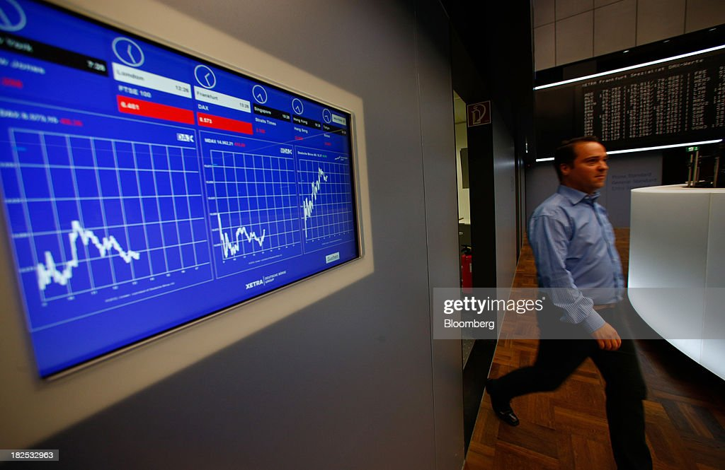 A trader walks past a monitor displaying the DAX index curve at the Frankfurt Stock Exchange in Frankfurt, Germany, on Monday, Sept. 30, 2013. Global stocks fell, trimming their biggest quarterly gain since the start of 2012, while the Japanese yen strenghtened before a potential U.S. government shutdown. Photographer: Ralph Orlowski/Bloomberg via Getty Images