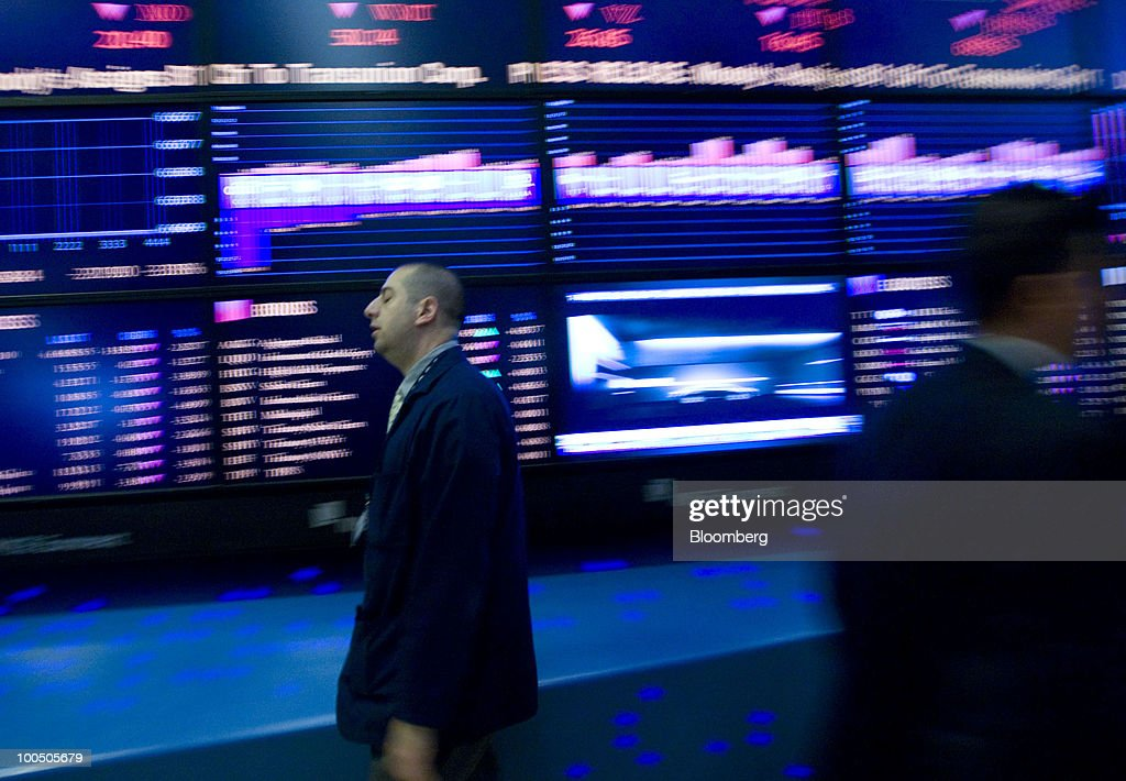 A trader walks past the board while working on the floor of the New York Stock Exchange in New York, U.S., on Tuesday, May 25, 2010. Stocks plunged from Tokyo to London and New York, dragging the MSCI World Index to a nine-month low, and commodities slid as concern grew that Spain's ailing banks signal a widening debt crisis and as tension mounted on the Korean peninsula. The German bund yield fell to its lowest since at least 1990. Photographer: Jin Lee/Bloomberg via Getty Images
