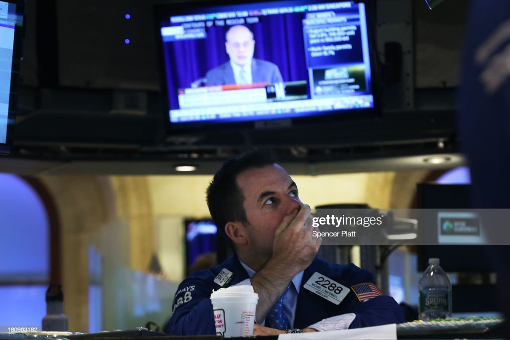 A trader watches the Federal Reserve Chairman Ben Bernanke, speaking at a news conference, on a television on the floor of the New York Stock Exchange on September 18, 2013 in New York City. As the economic outlook continues to remain precarious for the central bank, the Federal Reserve announced that it will continue its bond-buying program in full for at least another month. News of the decision sent stocks soaring with the Dow Jones industrial average up over 160 points in afternoon trading.