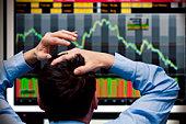 Trader watching stocks crash on screen