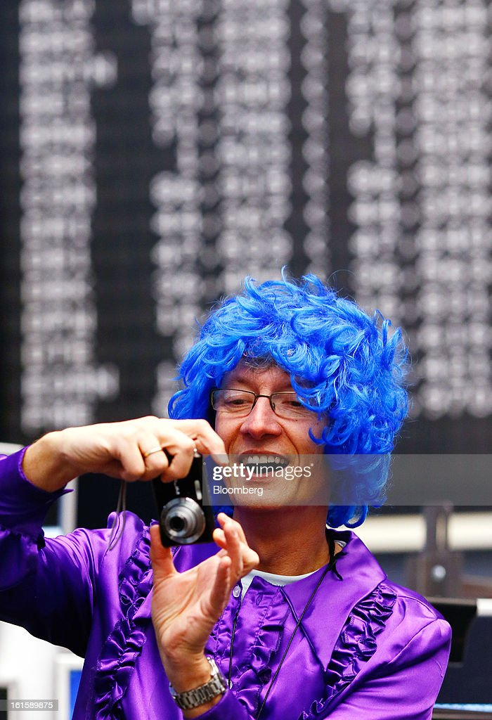 A trader wearing a blue wig and a purple dress takes a photograph of fellow traders while on the floor of the Frankfurt Stock Exchange during Carnival Tuesday in Frankfurt, Germany, on Tuesday, Feb. 12, 2013. Traders wear costumes as part of a long-standing tradition in honor of Germany's Carnival festivities. Photographer: Ralph Orlowski/Bloomberg via Getty Images