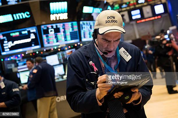 A trader wearing a 'Dow 20000' hat works on the floor of the New York Stock Exchange December 13 2016 in New York City The Dow Jones Industrial...