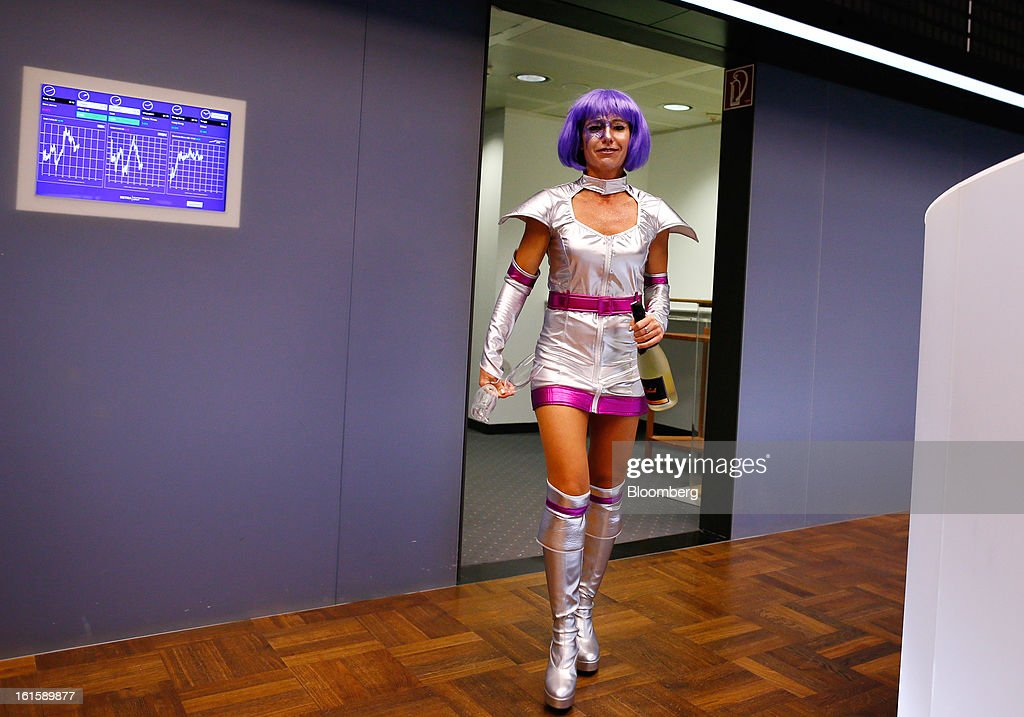 A trader wearing a purple wig and a Sci-Fi costume walks onto the floor of the Frankfurt Stock Exchange during Carnival Tuesday in Frankfurt, Germany, on Tuesday, Feb. 12, 2013. Traders wear costumes as part of a long-standing tradition in honor of Germany's Carnival festivities. Photographer: Ralph Orlowski/Bloomberg via Getty Images