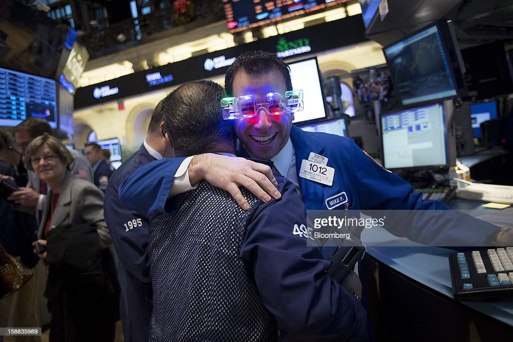 A trader wearing novelty glasses in the shape of '2013' hugs a co-worker at the New York Stock Exchange (NYSE) in New York, U.S., on Monday, Dec. 31, 2012. Most U.S. stocks gained, rebounding from a five-day slump, as investors weighed prospects for a compromise in federal budget talks. Photographer: Scott Eells/Bloomberg via Getty Images