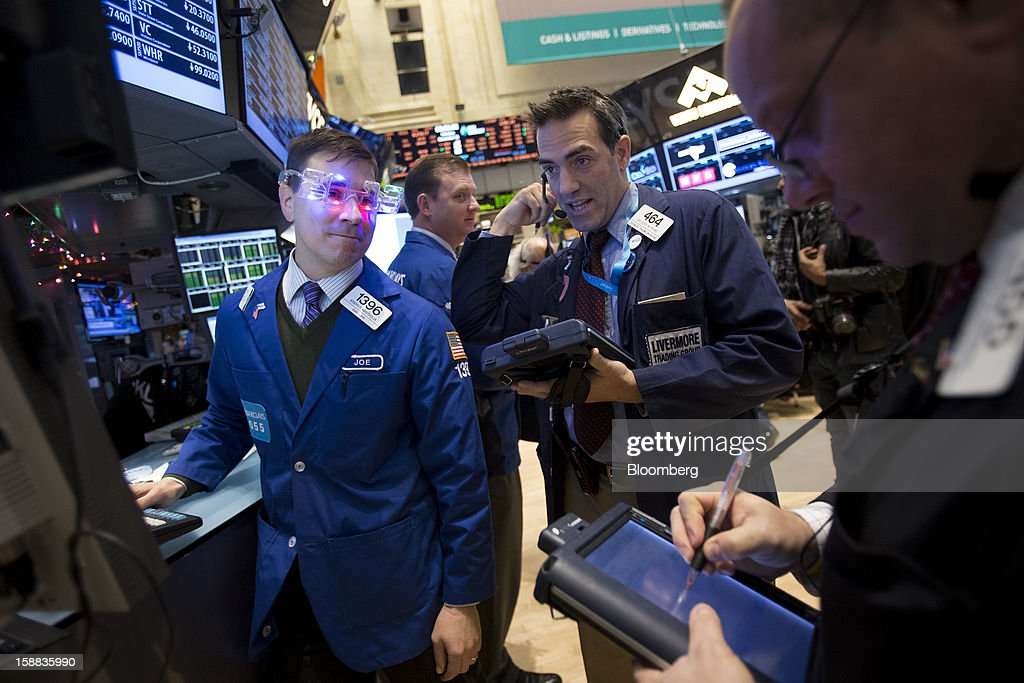 A trader wearing novelty glasses in the shape of '2013' works at the New York Stock Exchange (NYSE) in New York, U.S., on Monday, Dec. 31, 2012. Most U.S. stocks gained, rebounding from a five-day slump, as investors weighed prospects for a compromise in federal budget talks. Photographer: Scott Eells/Bloomberg via Getty Images