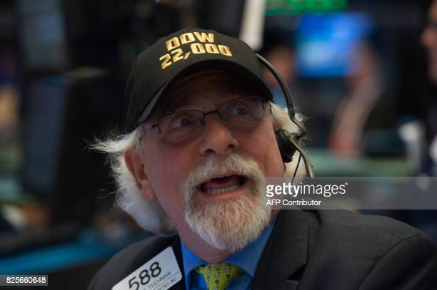 A trader wears a Dow 22000 points hat on the floor at the closing bell of the Dow Jones Industrial Average at the New York Stock Exchange on August 2...
