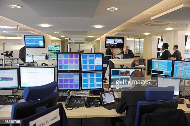 A trader works at a desk of the NYSE Euronext office in Paris on May 24 2011 NYSE Euronext is a EuroAmerican forprofit corporation that operates...