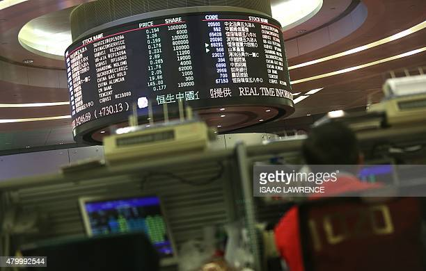 A trader works at the Hong Kong Stock Exchange on July 9 2015 Hong Kong shares ended the morning session 343 percent higher July 9 rebounding from a...